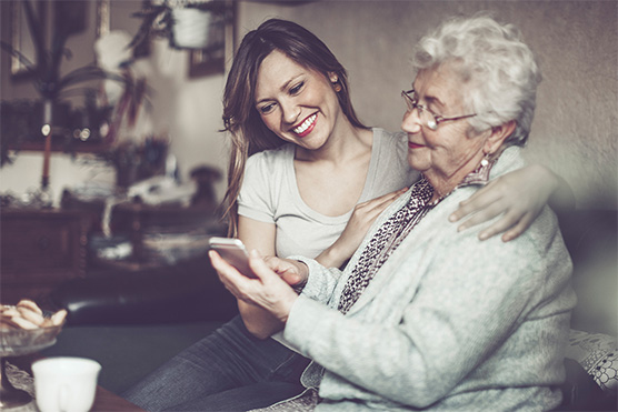Image, mother and daughter. Mother is looking at a smartphone in her hand